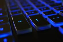 This image shows a computer keyboard with blue back lighting.