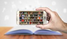 Hand holding a smart phone that shows a photo of a stack of library books.