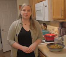 Lyndsey Maloney standing in her kitchen. There is a bowl of Lo Mein sitting on the counter beside her.