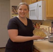Photo of Lyndsey Maloney holding a bowl of fettuccini alfredo.