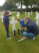 Two young boys join their father in cleaning the grave of PVT James Wise of Dillon