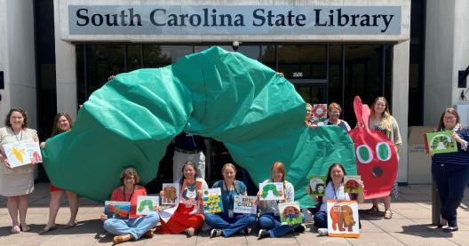 staff members holding up giant green caterpillar and eric carle books