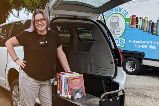 A library staffer from Keshaw County Library standing beside the upgraded programming van.