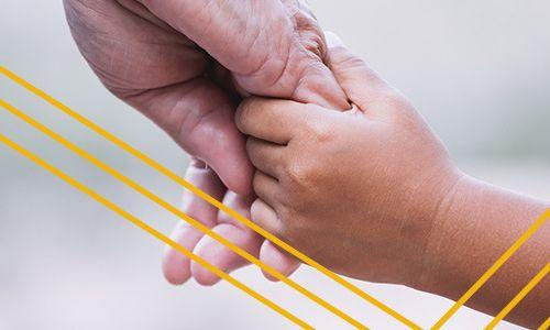 An adult hand holding a child's hand.